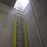Composite wall-mounted ladder with fall arrest system